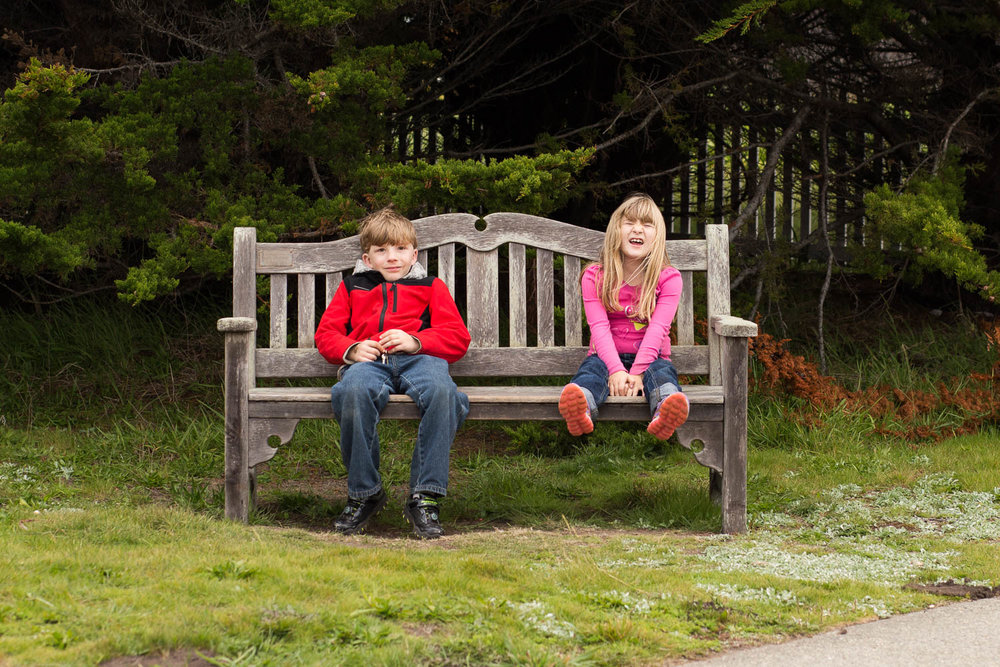 Siblings- boy and girl- sitting on a bench while one is smiling and one is crying and complaining.
