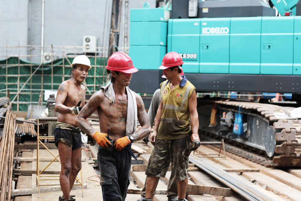 Cool tattoed workers in the streets of Hong Kong working to make the concrete jungle grow