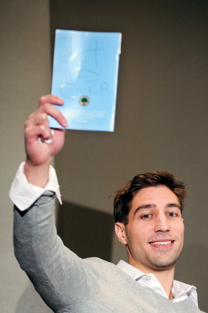 "At a 2013 press event in Columbia, Mo., Ryan Ferguson holds up a pamphlet with the message, ""It is over."" The writing from Zellner indicated his wrongful imprisonment for murder was over. Photo by Associated Press /Nick Schnelle, The Columbia Daily Tribune."