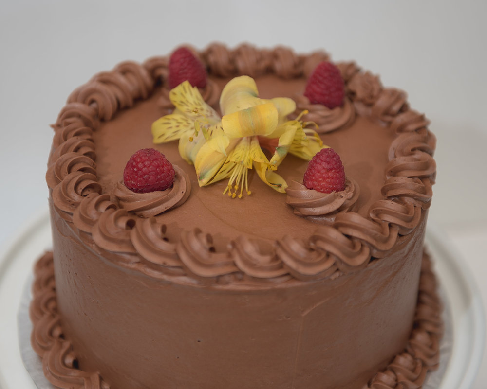 Double chocolate cake with raspberries. fresh flowers not included