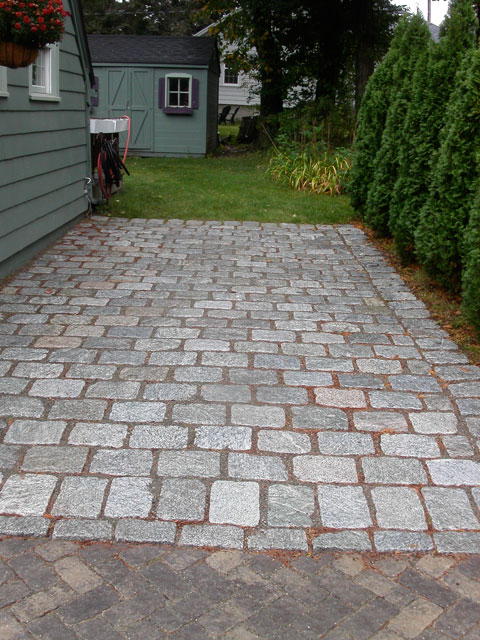 granite entrances featuring the paver walkway and driveway greatly enhance this home