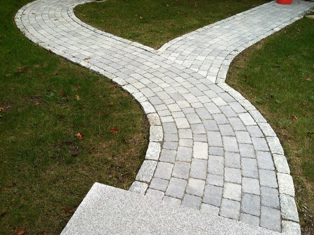 Multicolored Paver Patio Contains An Embedded Circle Kit As A Focal Point.