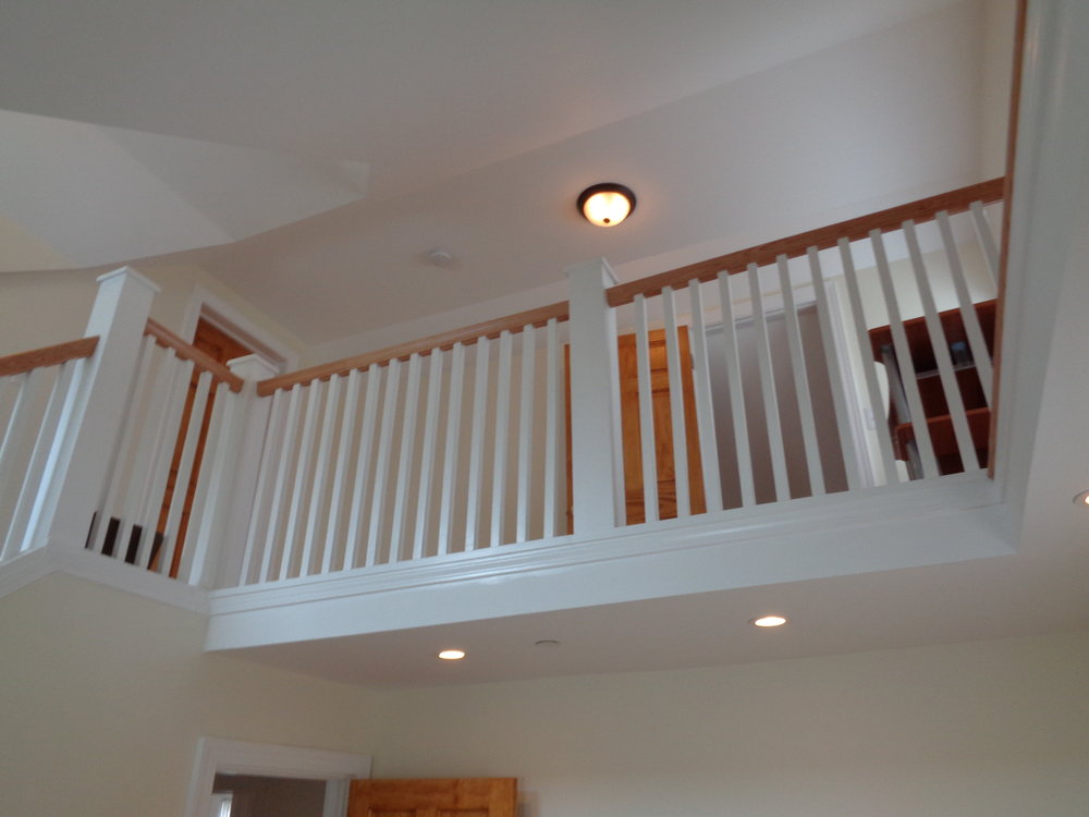 2nd Floor Newly Finished Banister Railing For Safety with New Lights. White Paint Finish on Walls.