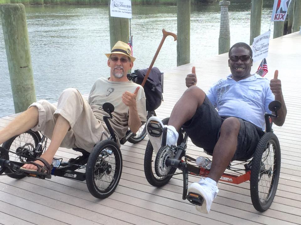 Riding a trike on the dock by the water.