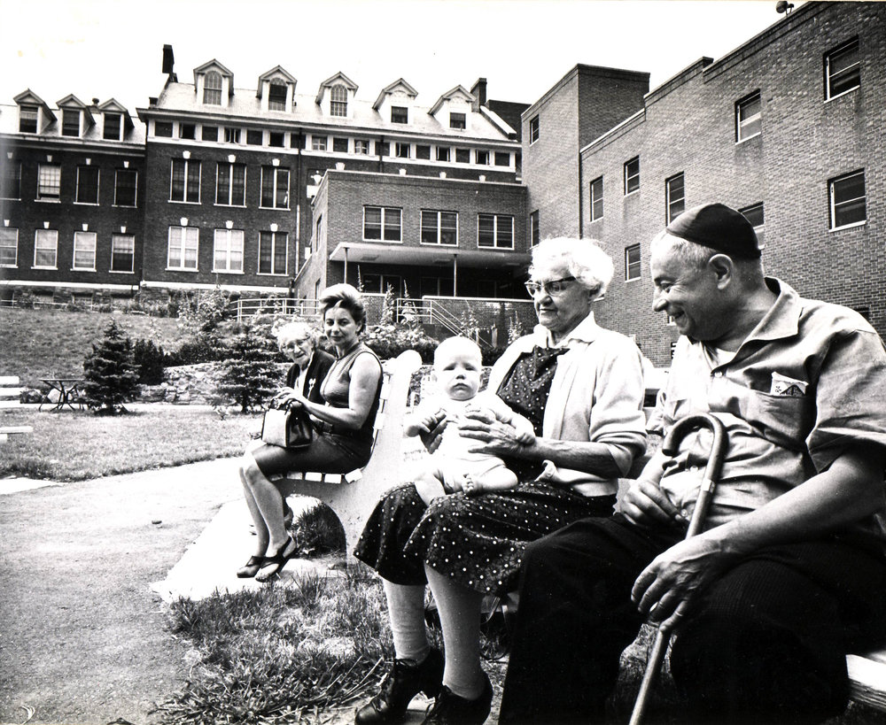 Residents with visitors outside the Irving and Pearl Stolz Pavilion, ca. early 1970s.
