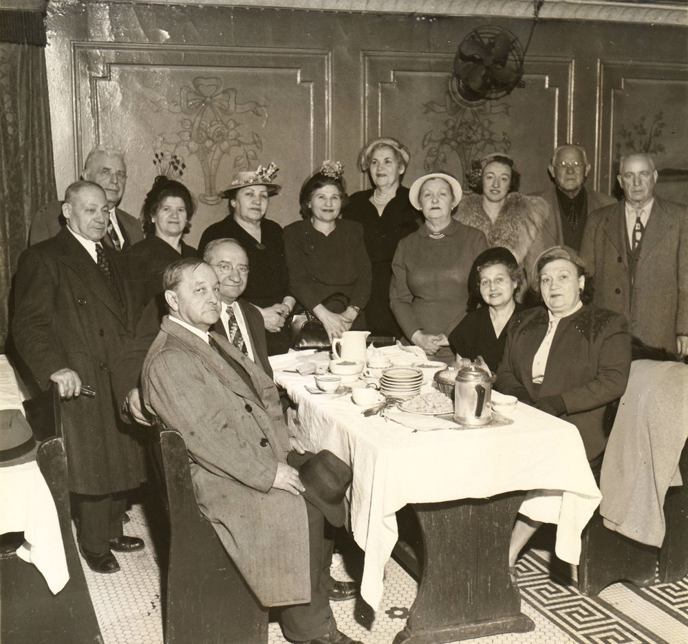 The lay leadership of the Home early in its history, were photographed in the dining room, including Harry Barschi (far left, standing) and Anna Barschi (second woman from left, standing), the great-grandparents of the Hebrew Home's current Board Chairman Jeffrey Maurer, before 1951.