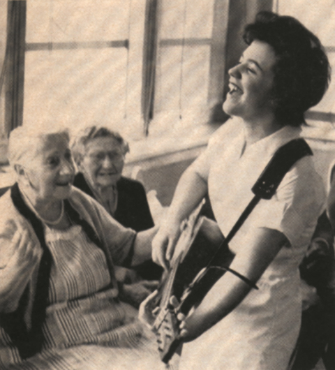 A musician plays guitar for residents in the 1960s, demonstrating the Hebrew Home's early commitment to the healing potential of the arts.