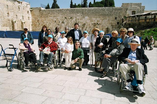 "Continuing to challenge the possibilities of aging, in 2004, Hebrew Home residents and staff embark on the first-ever overseas trip to Israel from a long-term care facility, appropriately dubbed the ""Chutzpah Mission."""