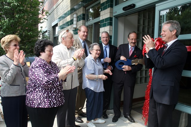 In 2012, Hudson House low-income senior housing opens with priority admissions for elder abuse victims. Congressman Eliot Engel cuts the ribbon as future residents and others at the ceremony, including Board member Herman (Sonny) Loeffler, former City Council Member G. Oliver Koppell, State Assemblyman Jeffrey Dinowitz, and Hebrew Home President and CEO Daniel Reingold, look on.