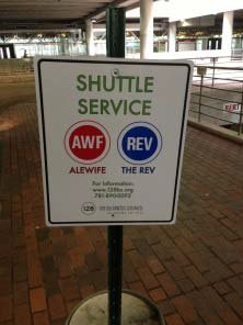 Photo of the Shuttle Service sign, which is standing upright and has a circular red logo that says AWF.