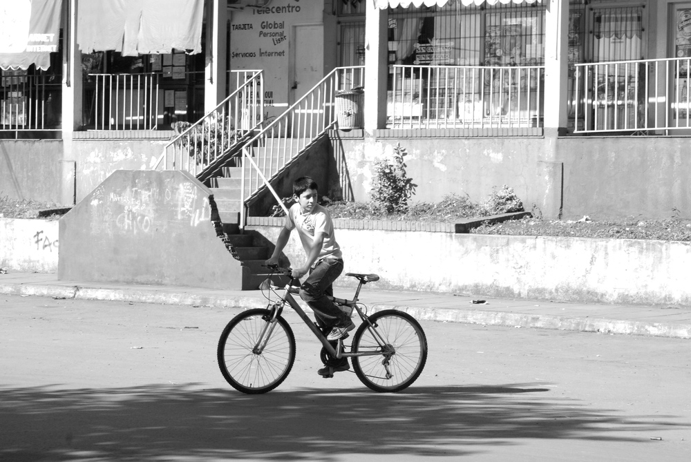 A boy riding his bike in front of the neighborhood mall on Las Calandrias Avenue.