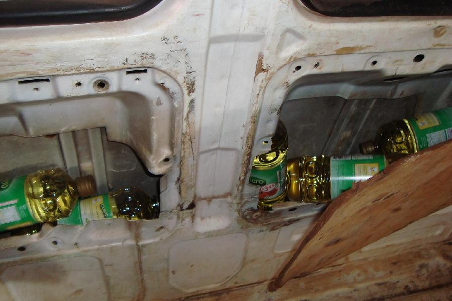Bottles of subsidized cooking oil found in a vehicle with hidden compartments. Courtesy of Aduana Argentina and La Voz de Cataratas.
