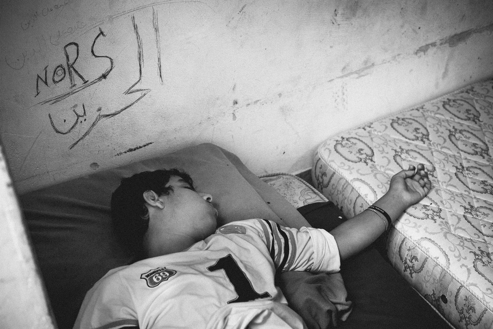 "Egyptians Room - O, the sleeping kid, wrote the name of his brother on the wall. Nors still lives in Egypt. The sign under means ""not happy"". He says it's because he doesn't like the place where he is living now."