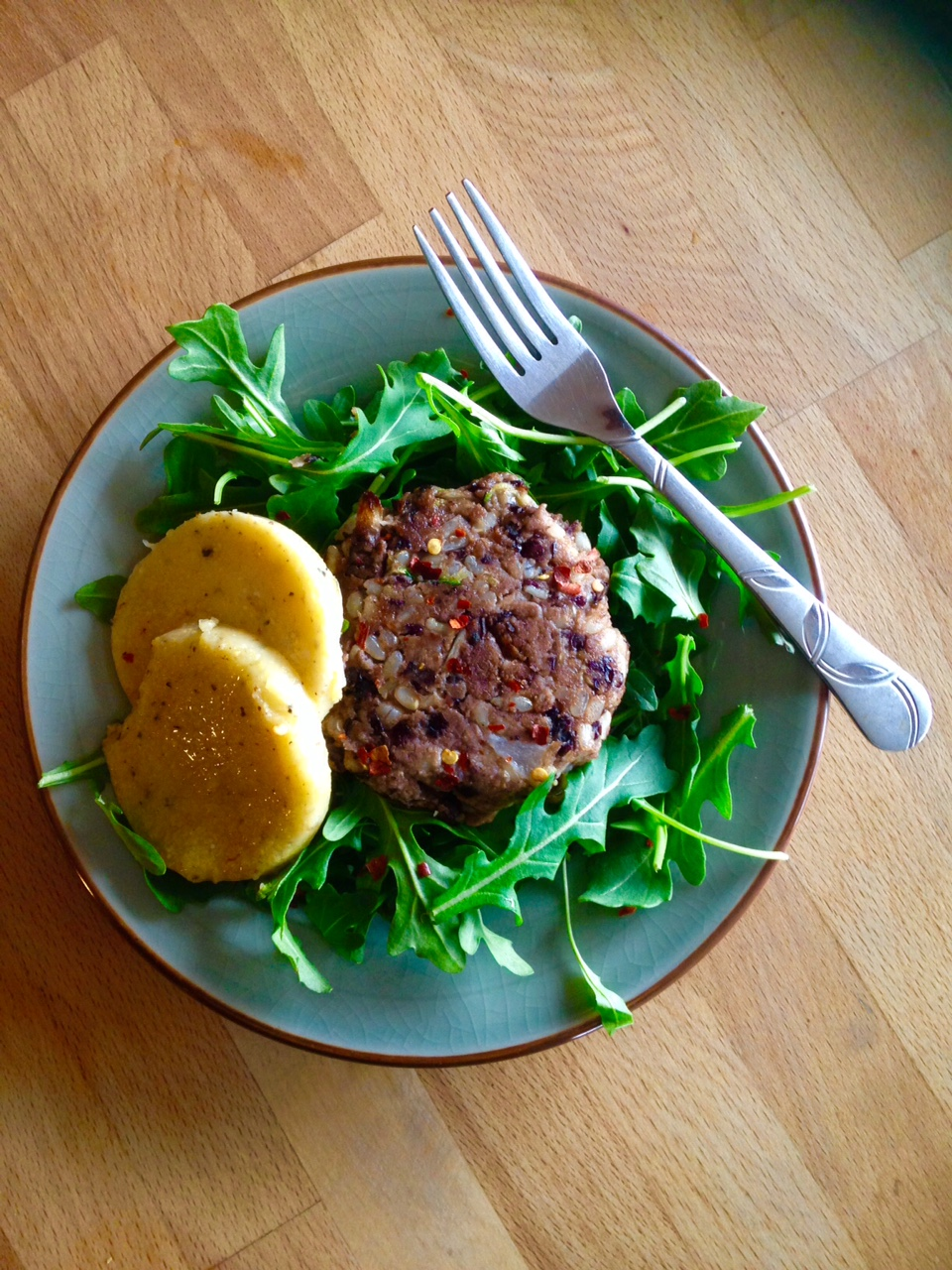 Kapha veggie burger served over a bed of arugula and a side of polenta.