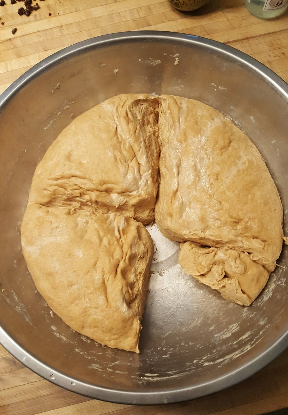 This photo shows the dough after it has risen overnight, a section is removed to begin the bagel making process.