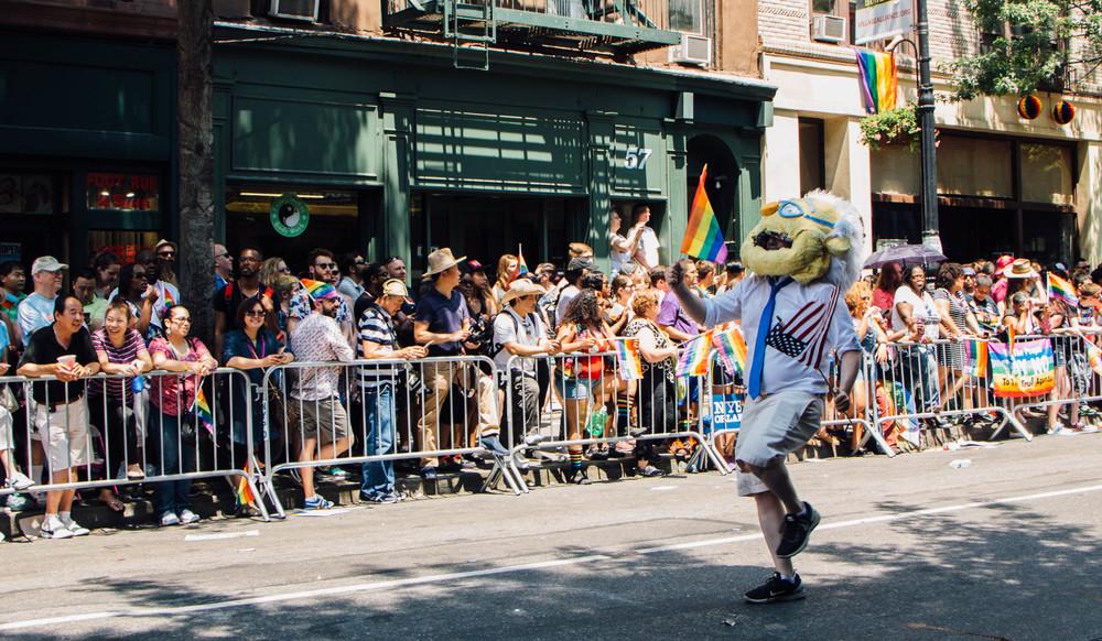 A Bernie Sanders mascot parades down 5th Avenue.
