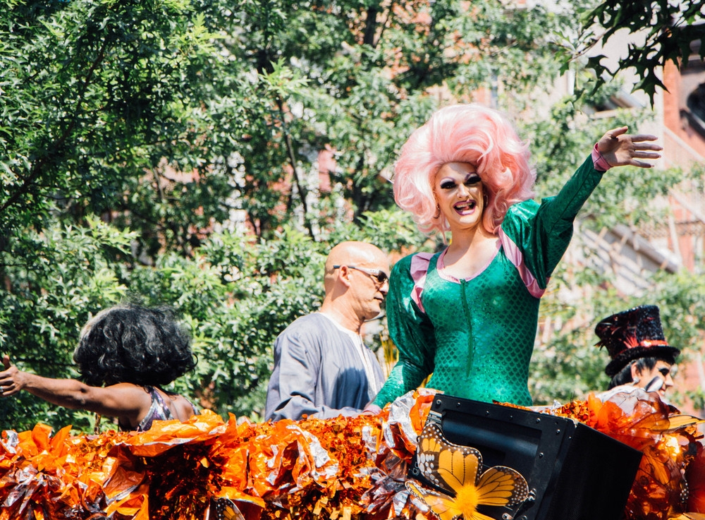 Drag queens wave from the tops of floats.