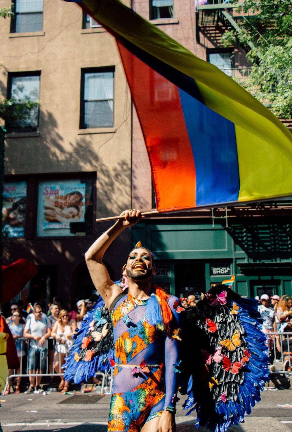 A Pride Parade marcher waves the flag of Ecuador.