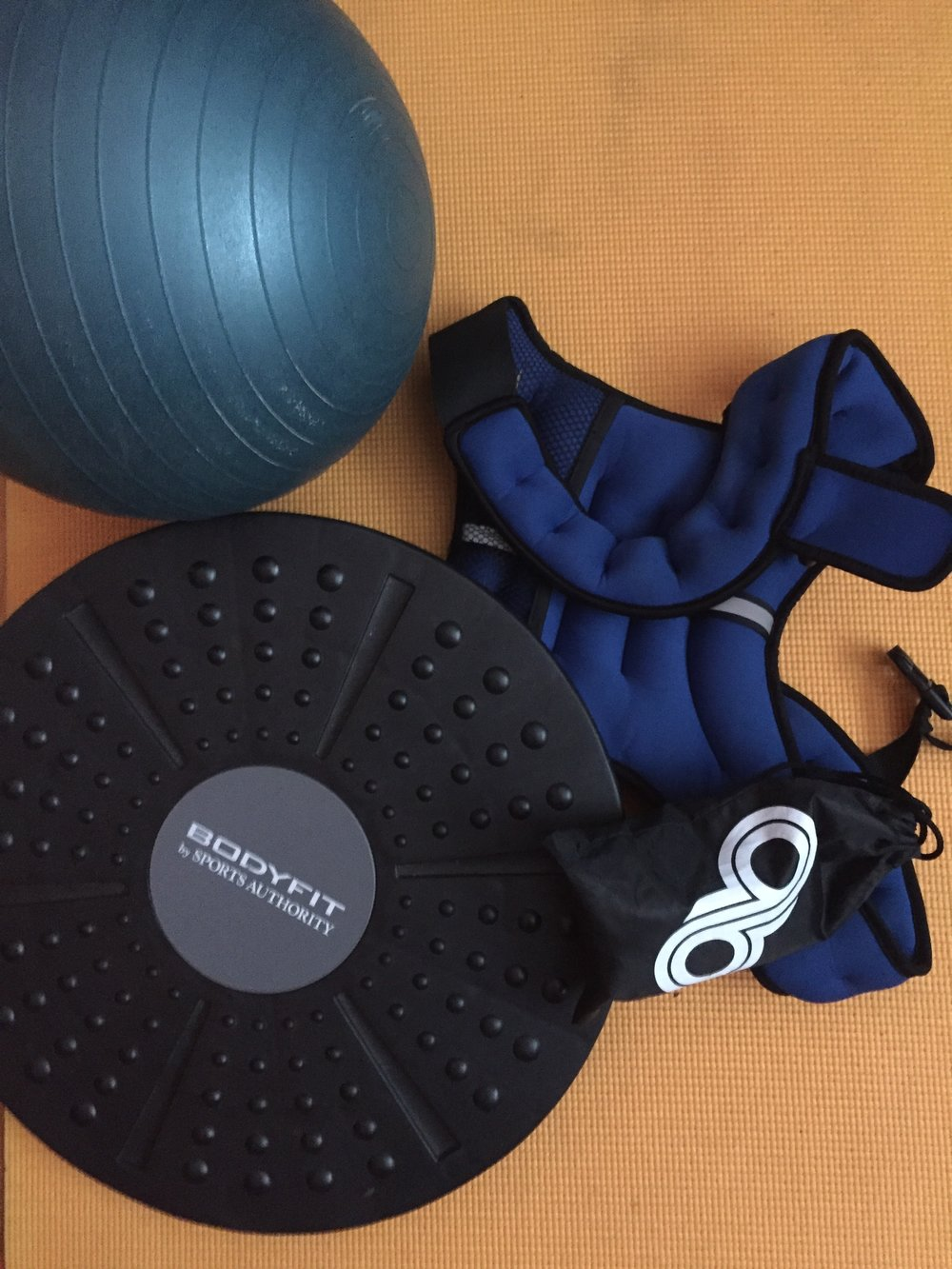 My gear for working out indoors when it's freezing out. A medicine ball, weight vest, balance board, stretch bands, and of course yoga mat. Tools for glute and core work. Simple and effective. When I do my outside workout it's pretty much the same tools, but I also use a battle rope and pull up bar. Maybe some rock rings too.