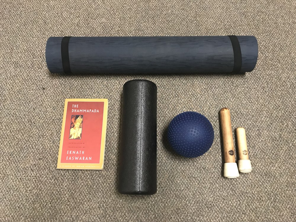 Morning routine gear, yoga mat, foam rollers,  Target Release  tools, and the Dhammapada, laid out for the next day.