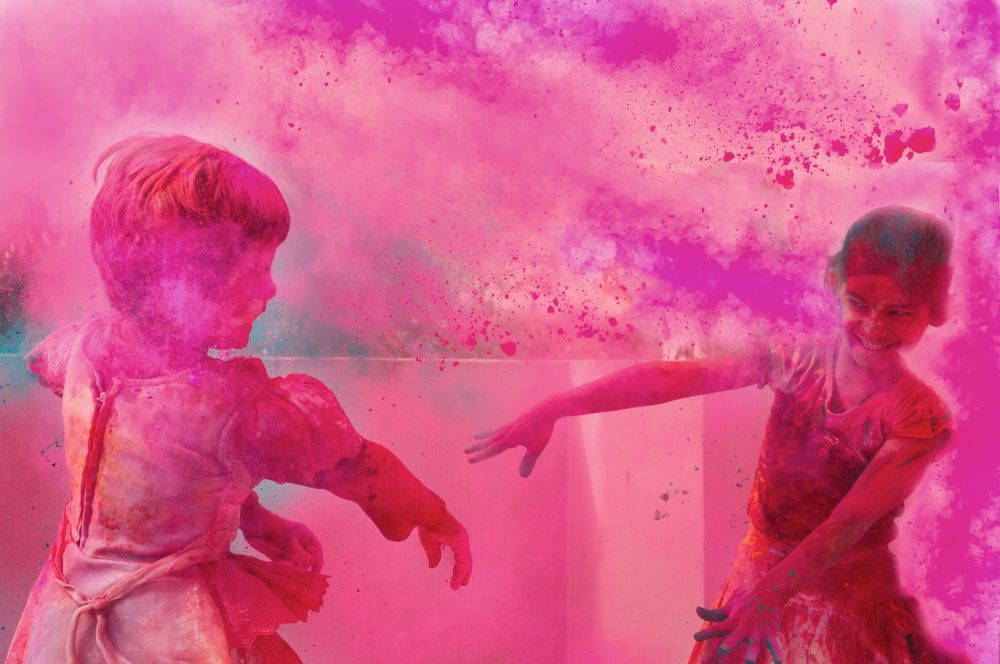 Two kids playing with G ulal powder on Holi, an Indian festival.