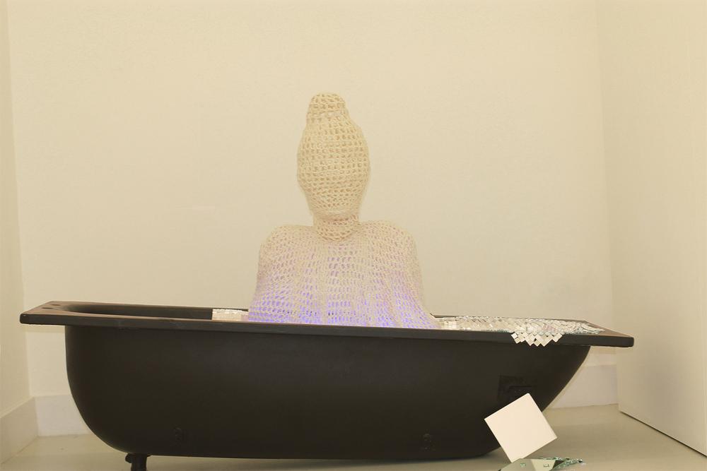Installation, a crocheted Buddha sculpture in a customized bath tub, 2010.