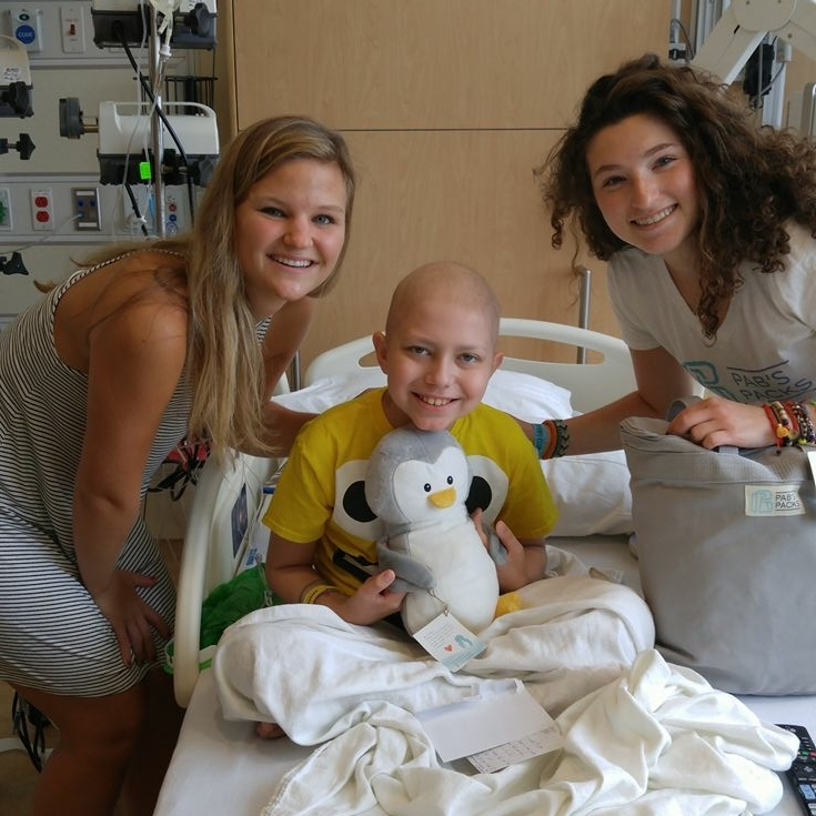 Abbie (left) and Pia (right) visiting a patient at Children's Minnesota this past summer.