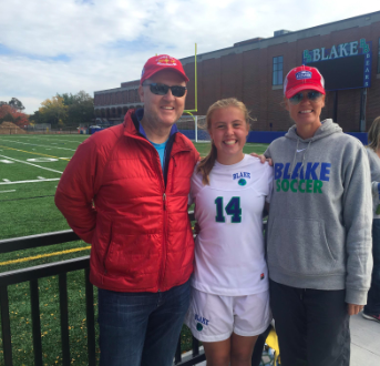 Lauren with her parents after being pulled up to play varsity soccer in ninth grade.