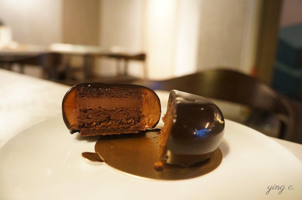 使用馬達加斯加、委內瑞拉與巴布亞紐幾內亞三款巧克力創作的純淨黑巧克力蛋糕。馬達加斯加巧克力突出清爽果酸,與後兩款巧克力的煙燻、堅果風味相互搭配;再加上慕斯、法式杏仁海綿蛋糕體(biscuit joconde)與巧克力奶酥脆粒(crumbles)的口感變化,讓這款蛋糕有著深厚不膩口的風味變化。