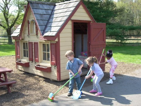 Children sweep outside a playhouse