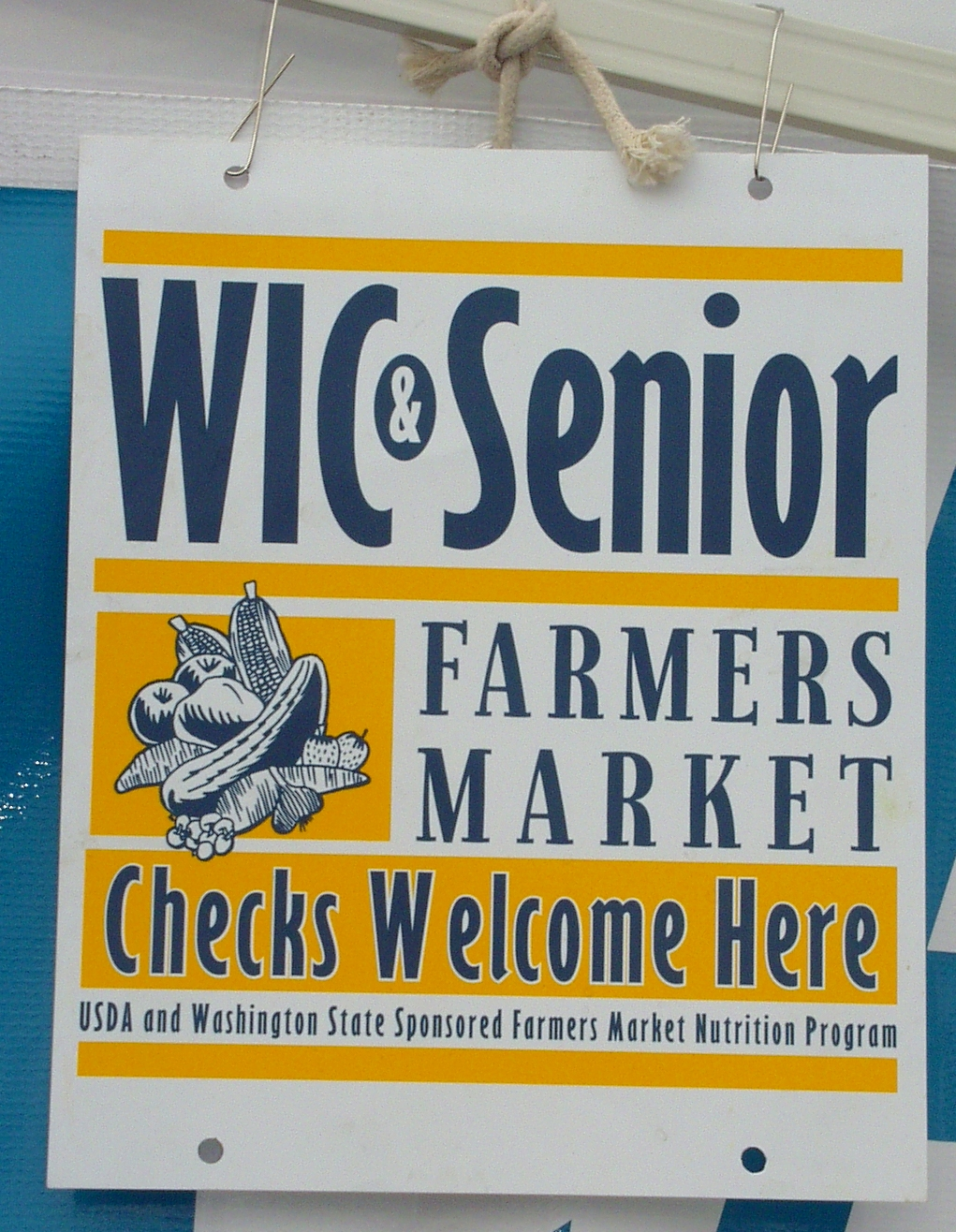 This sign hung at a farmers market vendor's booth means it accepts FMNP checks. Photo copyright 2009 by Zachary D. Lyons.