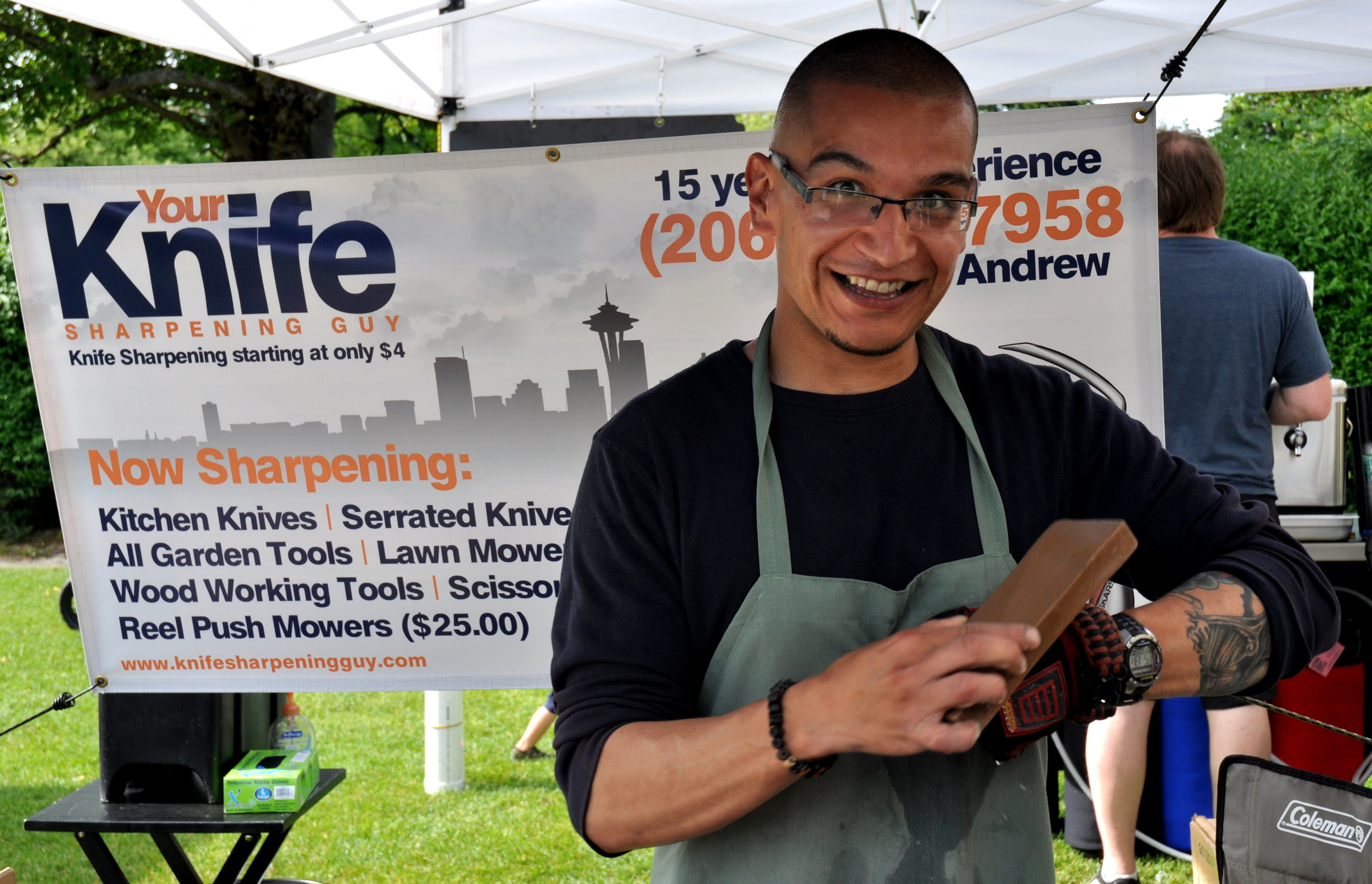 Andrew, Your Knife Sharpening Guy, sharpening knives at Wallingford Farmers Market this past summer. Photo copyright 2013 by Zachary D. Lyons.