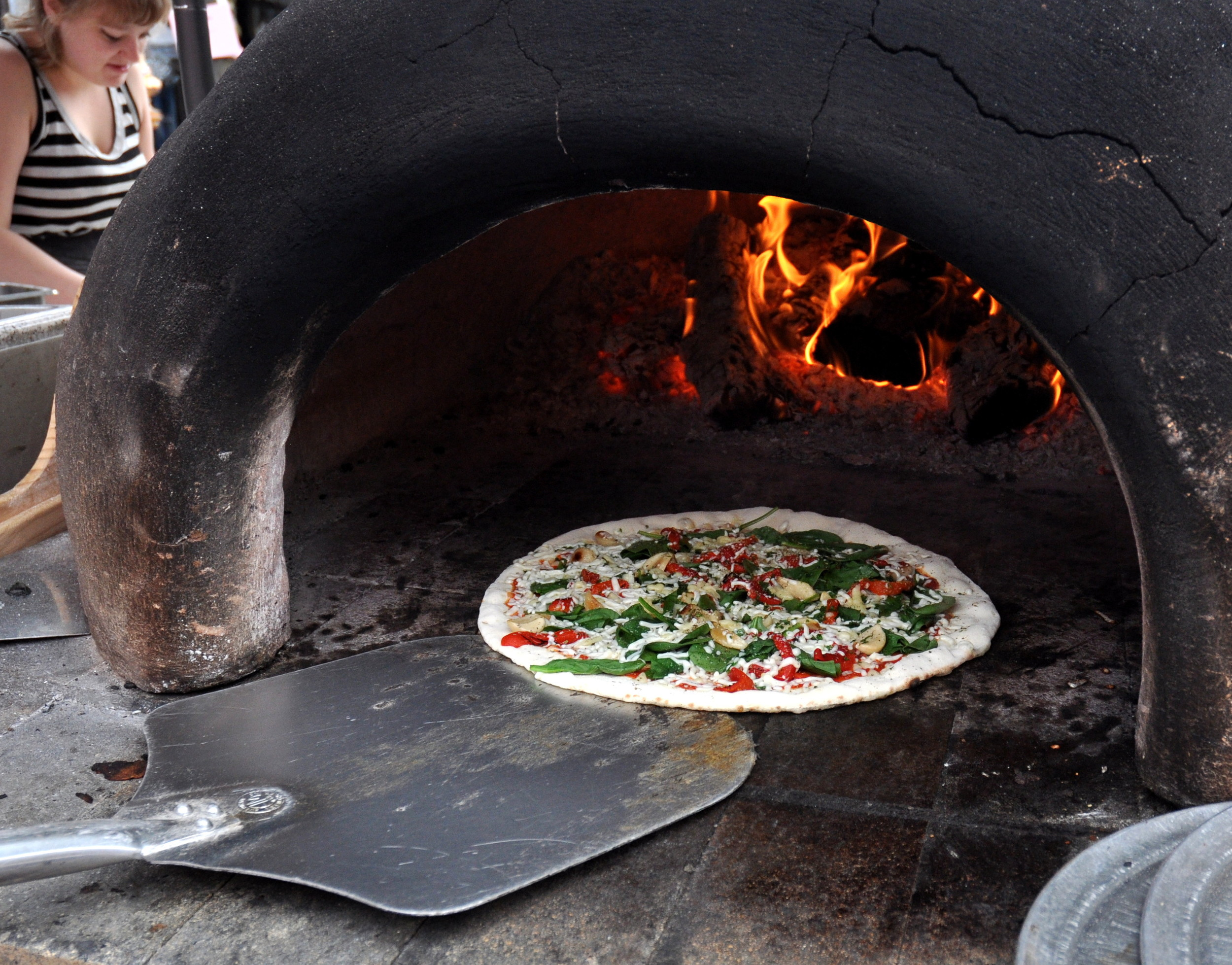 Loading pizza in the mobile oven at Veraci Pizza at Ballard Farmers Market. Copyright Zachary D. Lyons.