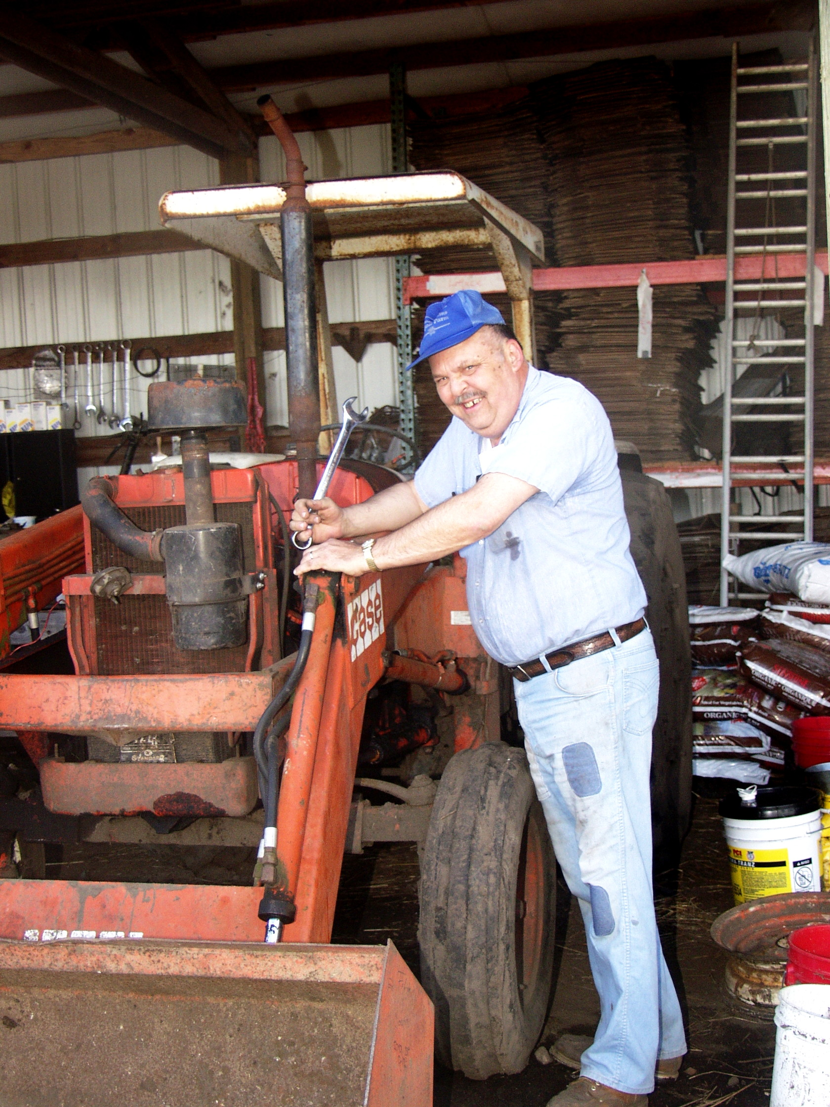 Bob Meyer of Stoney Plains Organic Farm working on his tractor. Photo courtesy Stoney Plains Organic Farm.