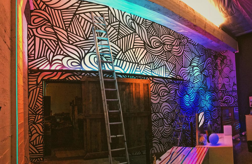 Mural progress picture. located in portland oregon, at ellumiglow. The mural changes color from the light shining on it, transitioning through a variety of colors and patterns. this allows the wall to look different depending on when it is viewed.