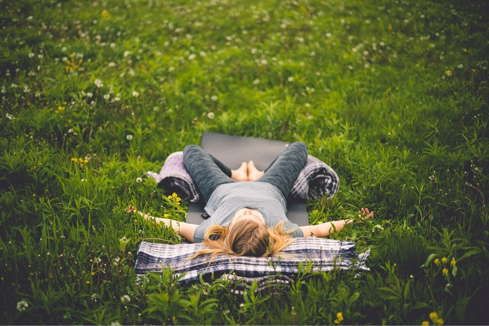 Image Description : A woman is laying on her back in a restorative yoga pose in the middle of a field. Her legs and head are supported by yoga blankets.