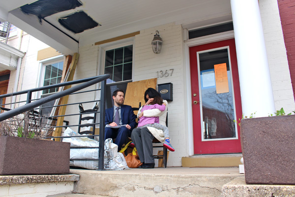 Crampton, Roman and their daughter Ama sitting on the porch of their home in March 2015. After a series of problems with the home, they moved out in Dec. 2013. (WAMU/Martin Austermuhle)
