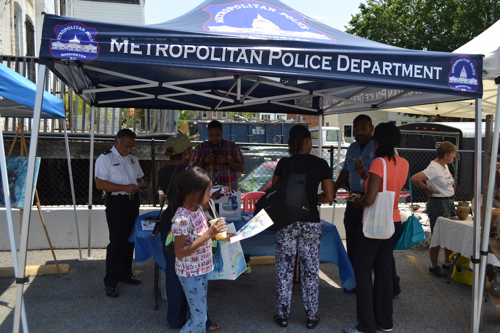MPD's community outreach booth with Commander Wilfredo Manlapaz, Officer Beam and Derek Stanton.