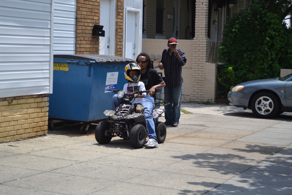 There is absolutely no reason to have an ATV on the sidewalk, let alone during a street festival. At least this genius put a helmet on the child.