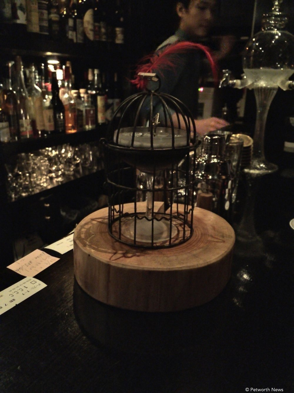 This drink features shaved charcoal and comes in a bird cage.