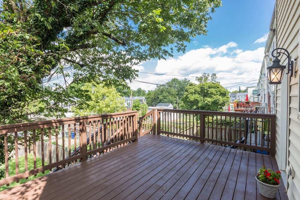 A large back deck overlooks a green lawn and parking pad.