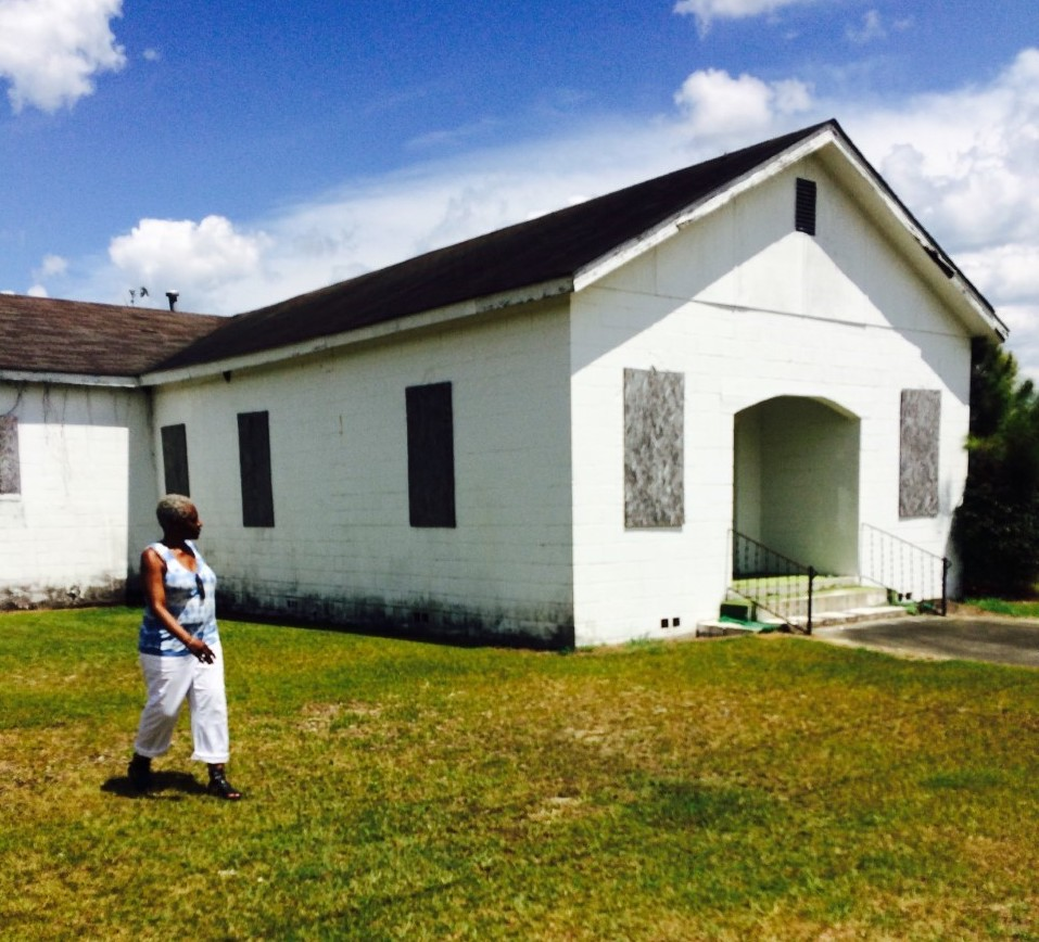 The author walking past an old school house.