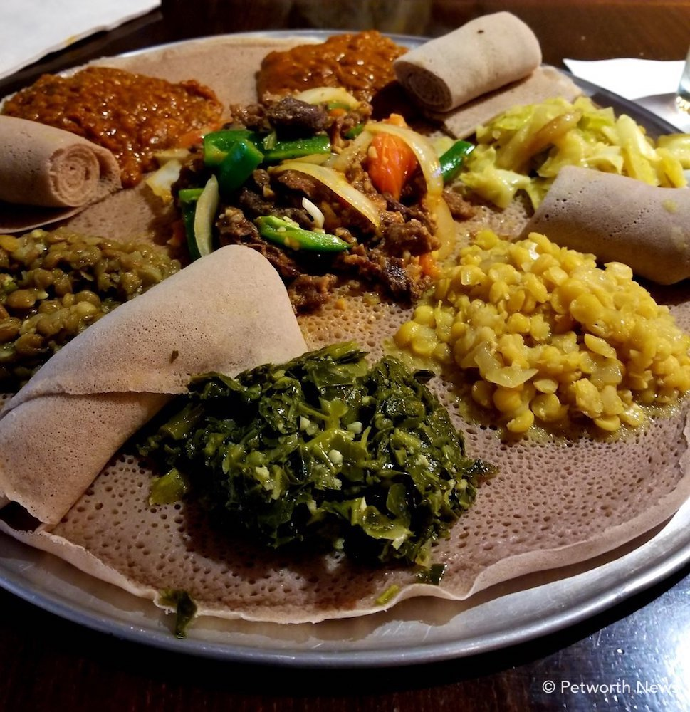 The Mignot veggie platter with lamb tibs, served in injera bread.