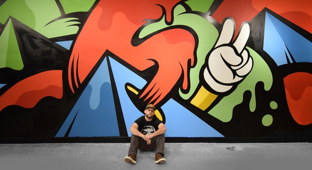 Matt Corrado in front of his artwork