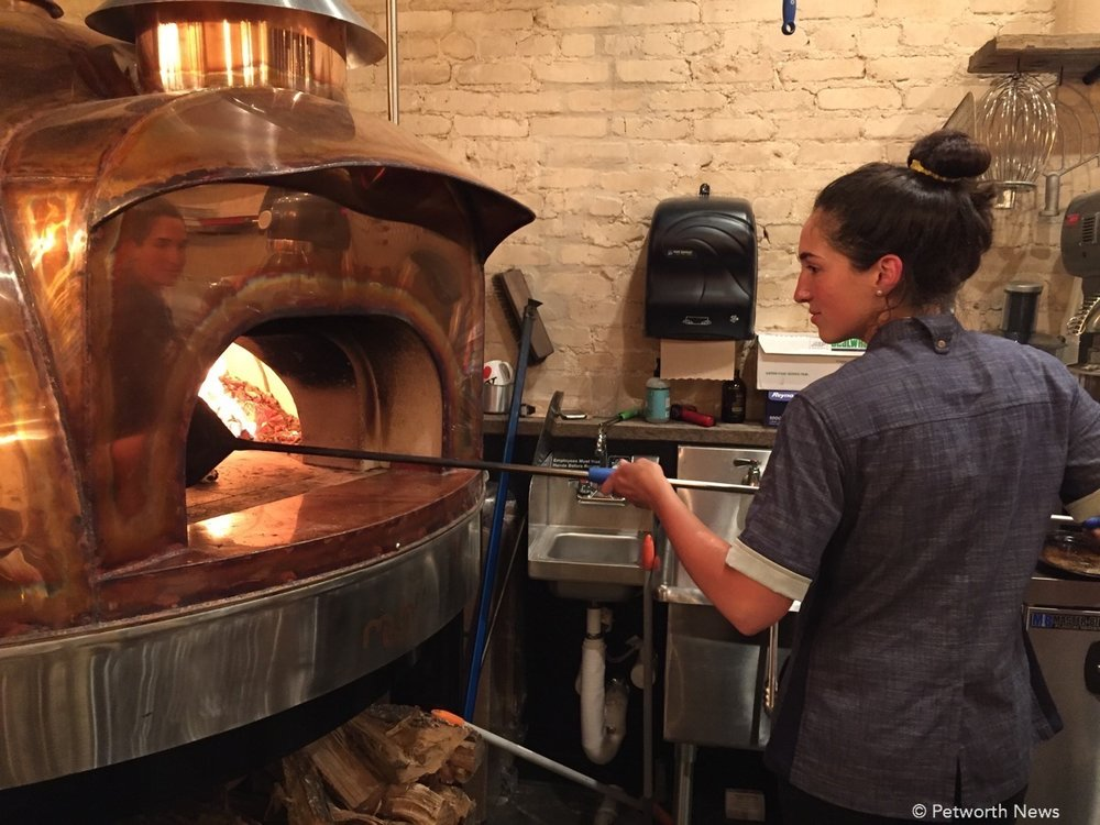 Dani Moreira taking a pizza out of the wood oven at Timber Pizza.