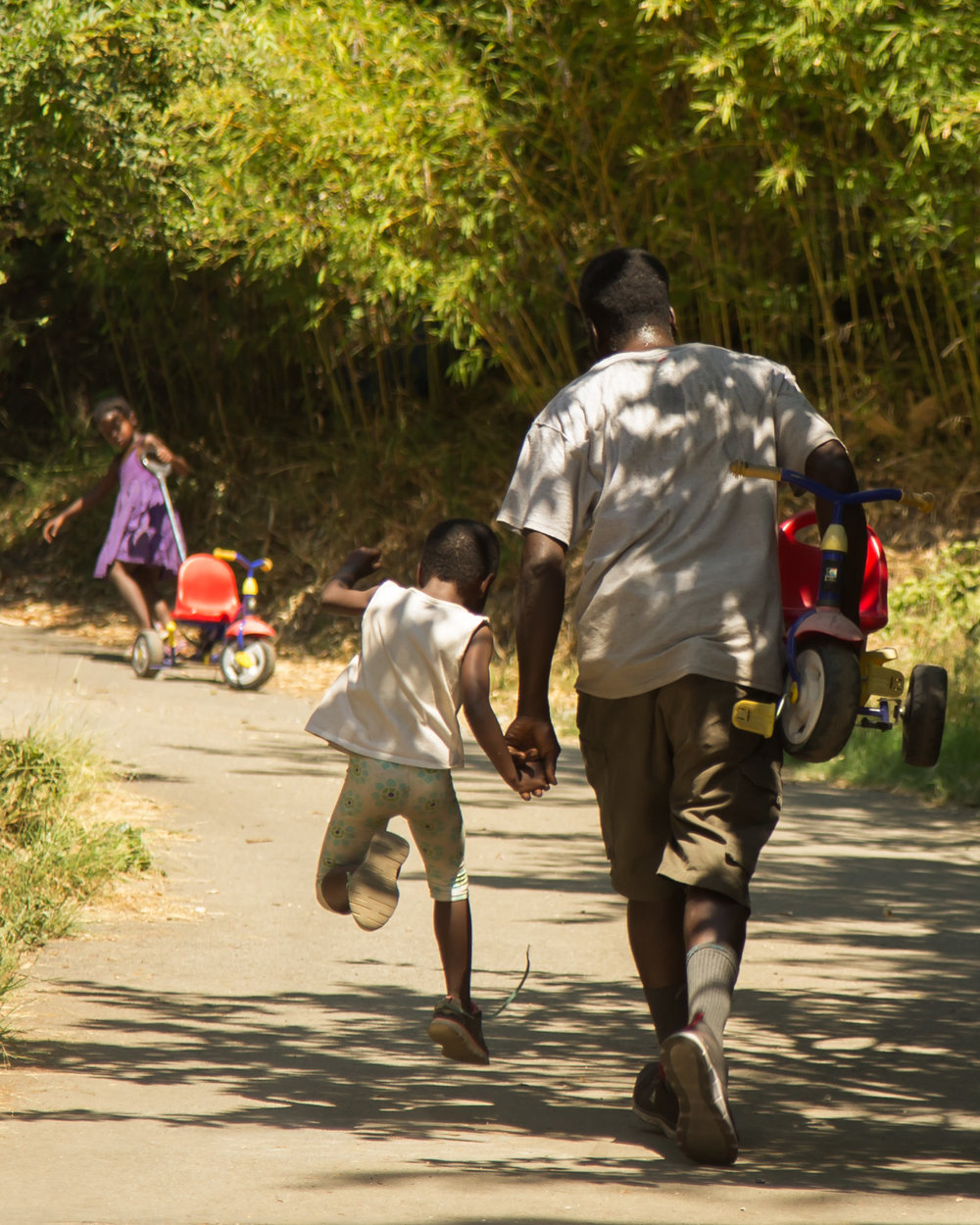 Laura's husband AJ and one of their daughters make another trek up the hill for the bicycle/tricycle race.