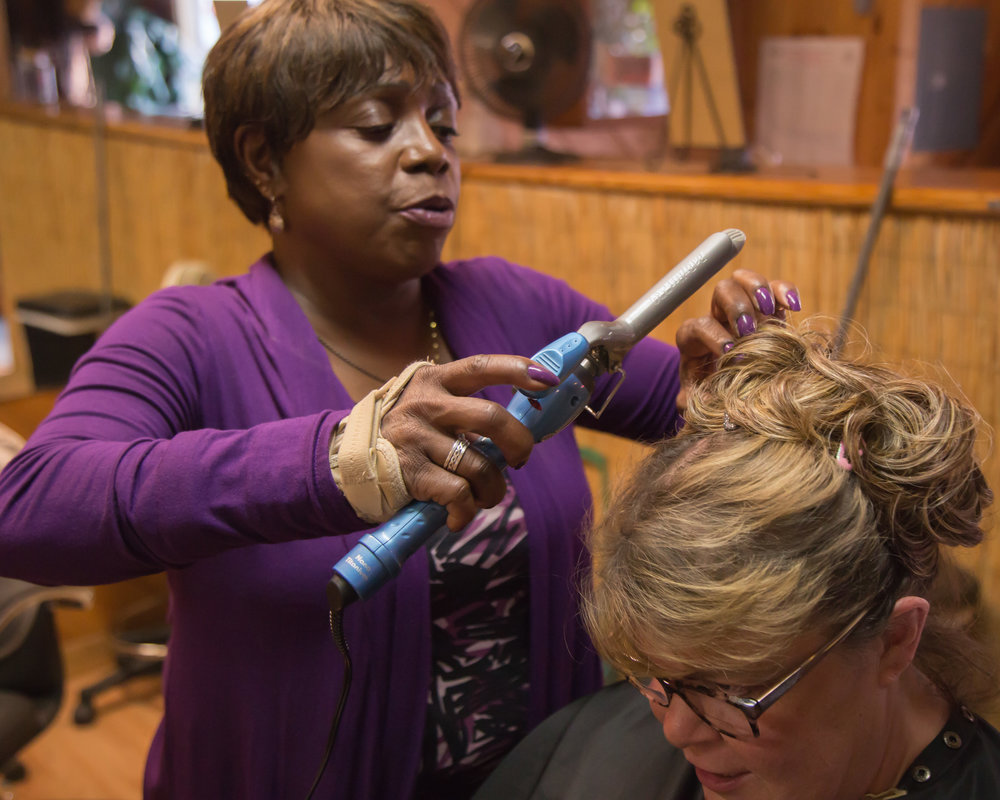Wanda styles and chats with Barbara Burns, owner of the Hair Hut in Boulder Creek where Wanda worked for years—the only Black stylist in San Lorenzo Valley. People still stop her and exclaim, 'Wanda, you used to do my hair!'