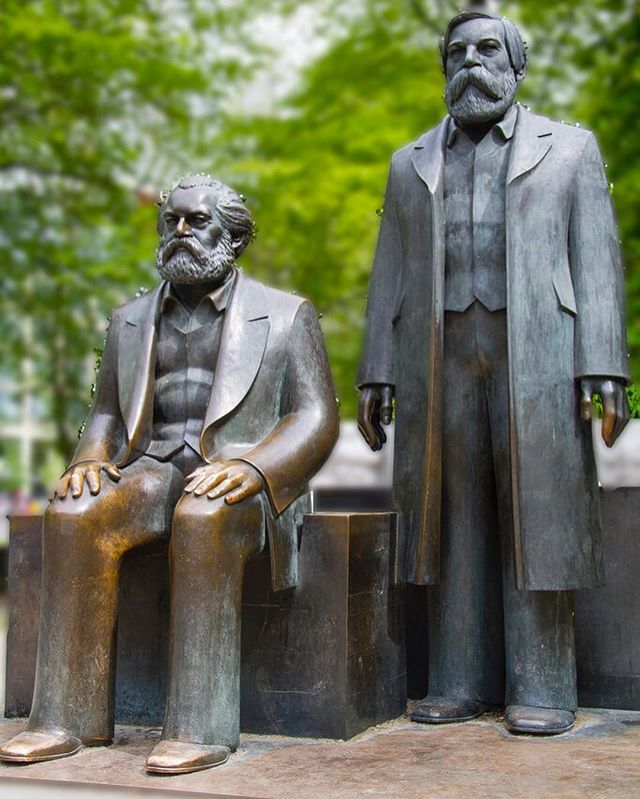 "Ludwig Engelhardt , Karl Marx and Friedrich Engels (1985) Marx-Engels Forum Berlin  Bronze  3.6m H + pedestal  Visual artist @cathy__wade selected today's post; this work is featured in a recent essay titled Rendered In/visable, 2018 the artist wrote for Future History following her recent visit to Berlin (please see the link below for the full essay). In Berlin one public art work that has survived a number of relocations and decades of political upheaval is Marx-Engels Forum. The sculpture is a consistent site for vandalism. During the 1990's the work had the legend ""We Are Blameless"" painted on it and was fondly referred to as ""The Pensioners"". The sculpture has been relocated from a tourist spot to a sleepy part of a park in Mitte. I went to visit the work this summer, after reading about it in Owen Hatherley's book ""Across the Plaza"". Removed from its original context I thought it would have come adrift, but there's something at play that activates it still. Over the decades, bronze sculptures oxidize unless they are touched. Marx and Engels' hands were golden and brassy, evidence of a series of gestures and connections with living citizens, which proved its continued meaning in the present. Excerpt from Rendered In/visable, 2018 by Cathy Wade  Ludwig Engelhardt was born in 1924 in Saalfeld. After an apprenticeship as a carpenter, he studied sculpture under Heinrich Drake at the Academy of Fine and Applied Arts (now: Academy of Arts Berlin-Weißensee) from 1951 to 1956. Engelhardt became then Drake's master student at the GDR Academy of Arts. Recommended by sculptor Fritz Cremer, Engelhardt became the lead artist for the Marx-Engels Forum and personally created the two central sculptures of Marx and Engels. He died on January 18, 2001 in Berlin.  Rendered In/visable, 2018 by Cathy Wade full essay: http://www.werk.org.uk/future-history-1//repository Photograph source: https://hiveminer.com/Tags/ludwige #karlmarx #friedrichengels #marxengelsforum #ludwigengelhardt #bronzesculpture #sculpture #politicalsculpture #greatpublicart #publicart #artoftheday #gestures"