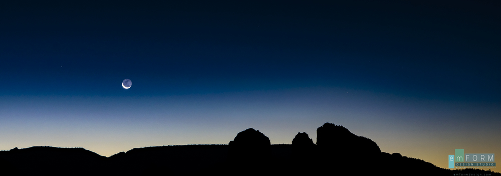 The crescent moon rise over the silhouette of Cathedral Rock in Sedona Arizona.