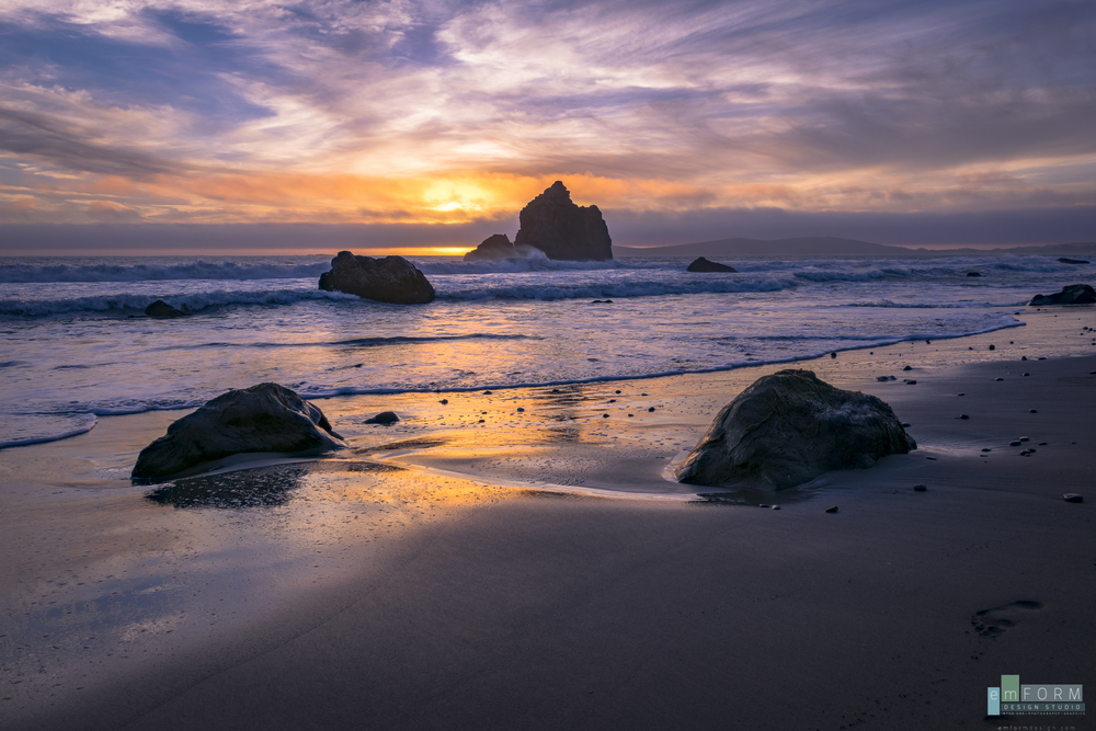 A few clouds obstruct and enhance the colors of the sun just before sunset at Pinnacle Gulch Beach CA
